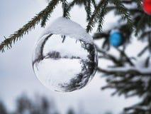 在一棵街道树的白色和色的圣诞节球在雪下 库存图片