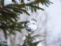 在一棵街道树的白色圣诞节球在雪下 免版税库存照片