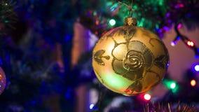 在一棵装饰的圣诞树的背景的金黄中看不中用的物品与圣诞灯的 免版税库存照片
