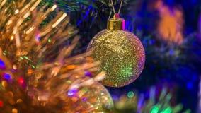 在一棵装饰的圣诞树的背景的金黄中看不中用的物品与圣诞灯的 库存图片