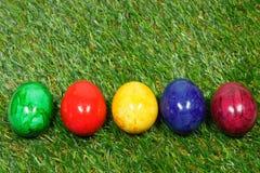 在一棵综合性草的五颜六色的蛋谎言 免版税图库摄影