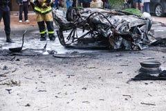 在一次事故以后的被烧的汽车在路 附近站立的消防队员 事故的报告文学图片 免版税图库摄影