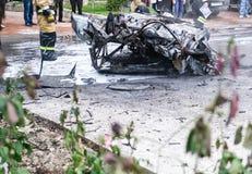 在一次事故以后的被烧的汽车在路 附近站立的消防队员 在街道的报告文学图片 免版税图库摄影