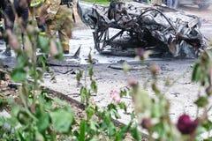 在一次事故以后的被烧的汽车在路 附近站立的消防队员 报告文学图片 免版税库存照片