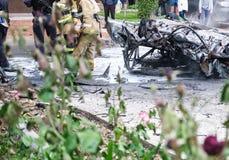 在一次事故以后的被烧的汽车在路 附近站立的消防队员 报告文学图片 库存照片