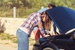 在一次汽车故障以后的年轻夫妇在路的边 库存图片