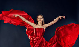 在一次红色丝绸礼服飞行的美好的激动人心的妇女跳舞 库存图片