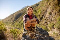 在一次远足期间的女性采取的休息在山 库存照片