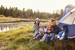 在一次野营的亚洲家庭在他们的帐篷之外放松 库存图片