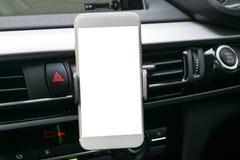 在一汽车使用的智能手机Navigate或GPS的 驾驶有智能手机的一辆汽车在持有人 移动电话屏幕白色 图库摄影