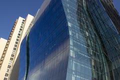 在一淡黄色古典一个旁边的现代弯曲的蓝色公司大厦 库存图片