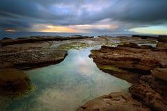 在一点海湾的风雨如磐的日出与在前景的rockpool 库存照片
