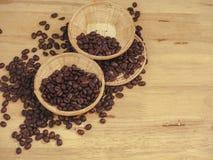 在一点篮子的咖啡豆在板条木头 免版税库存图片