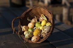 在一点篮子的复活节彩蛋木表面上 库存图片