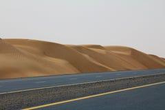 在一片沙漠旁边的一条空的路在迪拜,阿拉伯联合酋长国 免版税库存照片