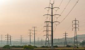 在一片耕地的电定向塔 免版税库存照片