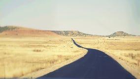 在一片黄色灌木沙漠的长的黑路 免版税库存照片