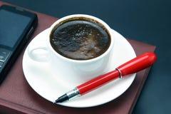 在一白色杯的红色笔无奶咖啡 图库摄影