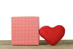 在一白色backg的一个木地板安置的红色心脏和礼物盒 免版税图库摄影