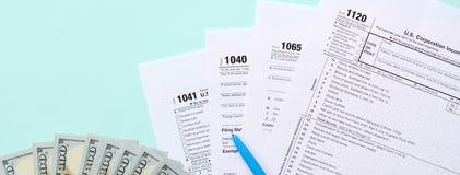 在一百元钞票和蓝色笔附近的报税表谎言在浅兰的背景 收入税单 库存照片