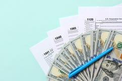 在一百元钞票和蓝色笔附近的报税表谎言在浅兰的背景 收入税单 免版税库存图片