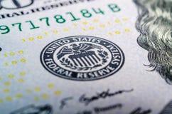 在一百元钞票特写镜头橡皮防水布的联储会系统标志 库存图片
