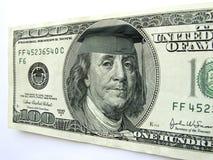 在一百元钞票的本富兰克林佩带的毕业盖帽 免版税库存照片