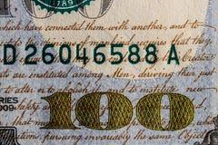 在一百元钞票的特写镜头金黄100和剧本背景的v 免版税库存照片
