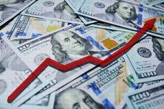 在一百元钞票背景的红色箭头图  库存照片