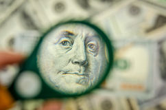 在一百美元的放大镜 免版税库存照片