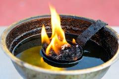 在一盏黄铜油灯的灼烧的火焰 库存图片