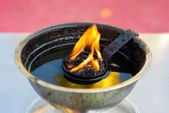 在一盏黄铜油灯的灼烧的火焰 免版税图库摄影