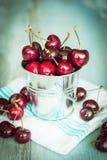 在一种小金属的樱桃在木背景用桶提 库存图片