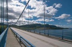 在一种渠道的一座桥梁在与小山和云彩的背景在一个晴天 免版税图库摄影