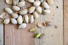 在一种粗麻布织品的开心果在一张自然木桌上在一个土气厨房里 库存照片