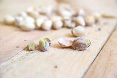 在一种粗麻布织品的开心果在一张自然木桌上在一个土气厨房里 免版税库存照片