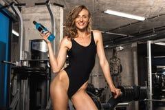 在一种锻炼以后的女孩与瓶补剂饮料 库存图片