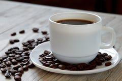在一粒杯子和烤豆的无奶咖啡在木suface 免版税图库摄影