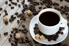 在一粒杯子和疏散烤豆的无奶咖啡在木背景 免版税库存图片