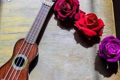 在一紫色吉他尤克里里琴脖子和fretboard的红色玫瑰 免版税图库摄影