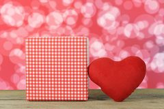 在一红色bokeh b的一个木地板安置的红色心脏和礼物盒 免版税库存照片