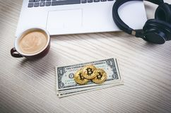 在一美元钞票的Bitcoin金黄硬币 办公室背景 咖啡、白色膝上型计算机、手机和金钱 金钱平衡 免版税库存图片