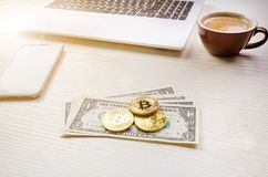 在一美元钞票的Bitcoin金黄硬币 办公室背景 咖啡、白色膝上型计算机、手机和金钱 金钱平衡 免版税库存照片