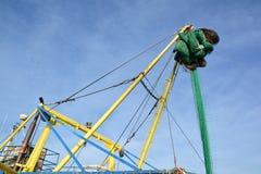 在一艘拖网渔船的捕鱼网反对蓝天 图库摄影