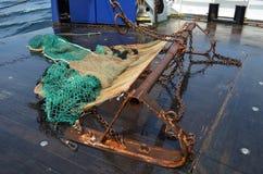 在一艘捕鱼船的甲板的拖网和挖泥机 免版税库存照片