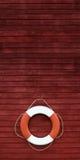 在一艘木船一边的红色和空白救生圈 库存图片