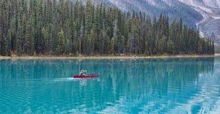 在一艘皮船的一个人航行在一个鲜绿色湖 免版税库存图片