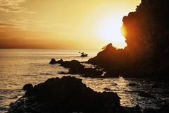 在一艘皮船的一个人航行在日落期间 库存照片