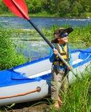 在一艘皮船附近的男孩在河 免版税库存图片