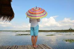 在一艘竹木筏的妇女伞 免版税库存图片